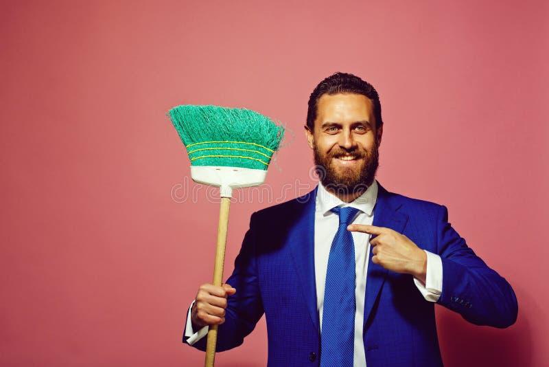 Biznes, dom, przystojny szczęśliwy mężczyzna i biznesmen z miotłą, zdjęcie stock