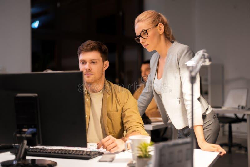 Biznes drużyna z komputerowy pracującym przy biurem póżno obrazy stock