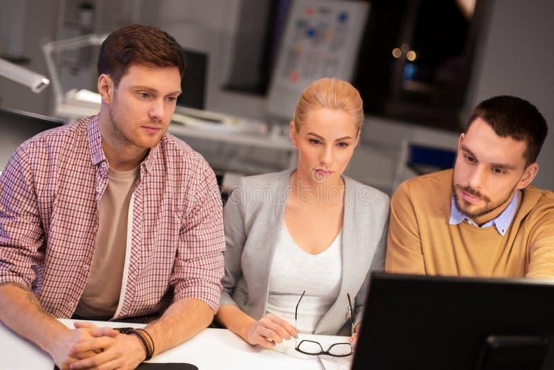 Biznes drużyna z komputerowy pracującym przy biurem póżno obrazy royalty free