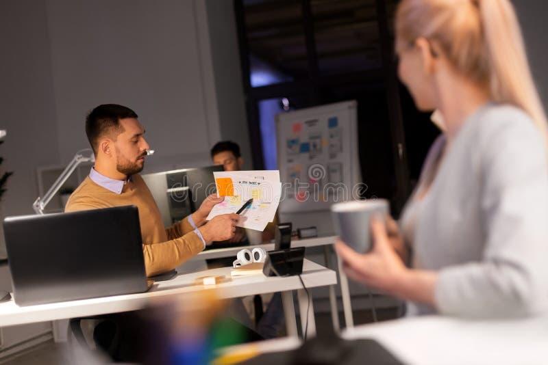Biznes drużyna z papierami pracuje póżno przy biurem zdjęcie stock