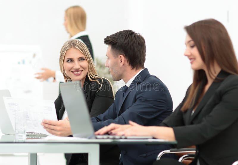 Biznes drużyna dyskutuje nową informację, stoi przed otwartym laptopem fotografia stock