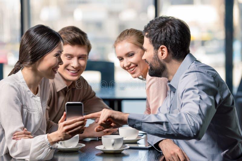 Biznes drużyna na spotkaniu dyskutuje projekt z smartphone w kawiarni fotografia stock