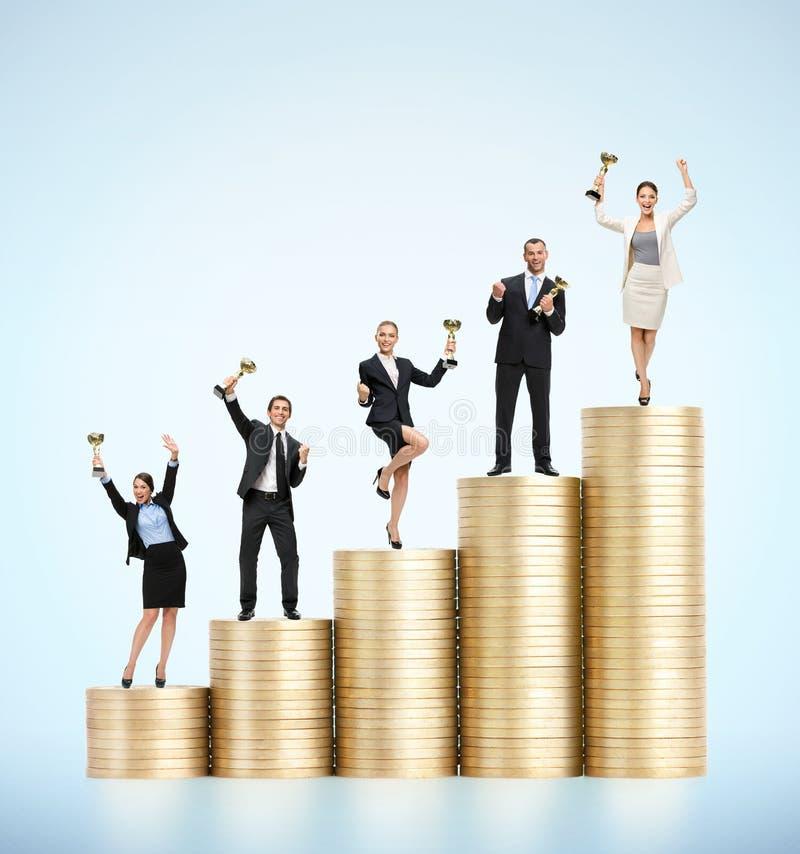 Biznes drużyna stoi na schodkach złociste monety z filiżankami zdjęcia stock