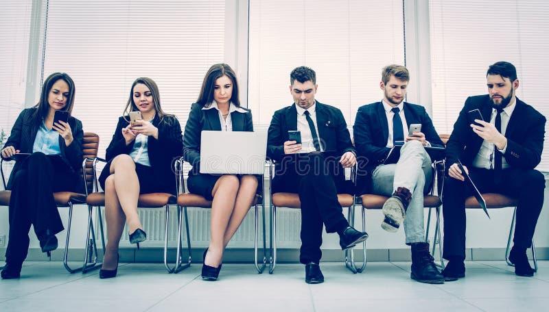 Biznes drużyna z laptopu i smartphone obsiadaniem na kanapie wewnątrz obraz royalty free