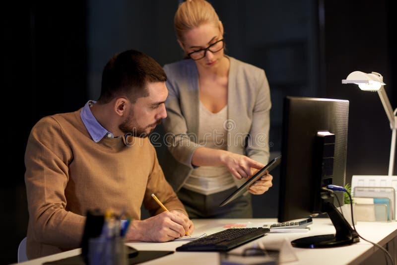 Biznes drużyna z pastylka komputerem osobistym przy nocy biurem obraz royalty free