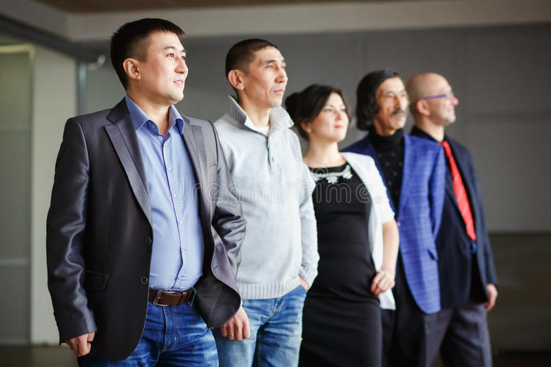 Biznes drużyny pięć ludzie, mężczyzna i kobieta patrzeje w odległość, wszystko są za ich liderem pochodzi wśrodku obrazy stock