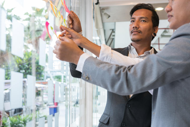 Biznes drużyny spojrzenie przy adhezyjnymi notatkami na szklanej ścianie w meetin fotografia royalty free