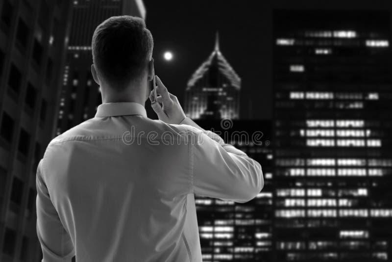 Biznes, ludzie i biurowy pojęcie, - biznesmen dzwoni na mądrze telefonie nad biurowym blisko z okno w nocy zdjęcie stock