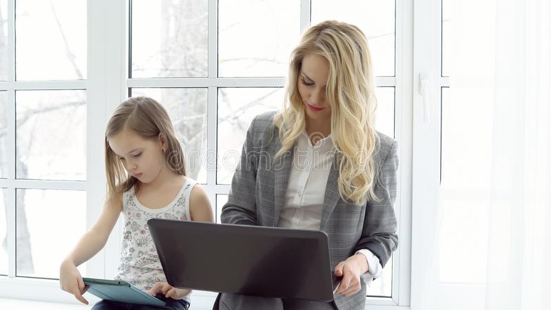 Biznes matka z laptopu i córki obsiadaniem okno zdjęcia royalty free