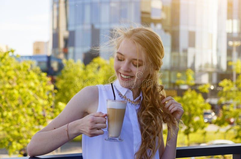 Biznes, napoje, czas wolny i ludzie poj??, - u?miechni?ta kobieta pije kaw? nad budynkiem biurowym w mie?cie zdjęcie stock