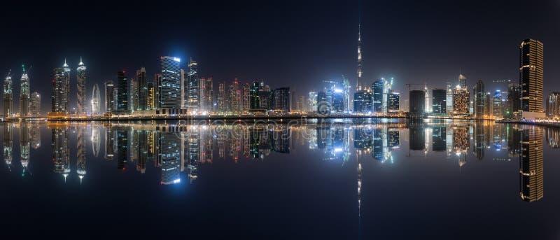 Biznes podpalana linia horyzontu z odbiciem w wodzie przy nocą, Dubaj, UAE obrazy royalty free