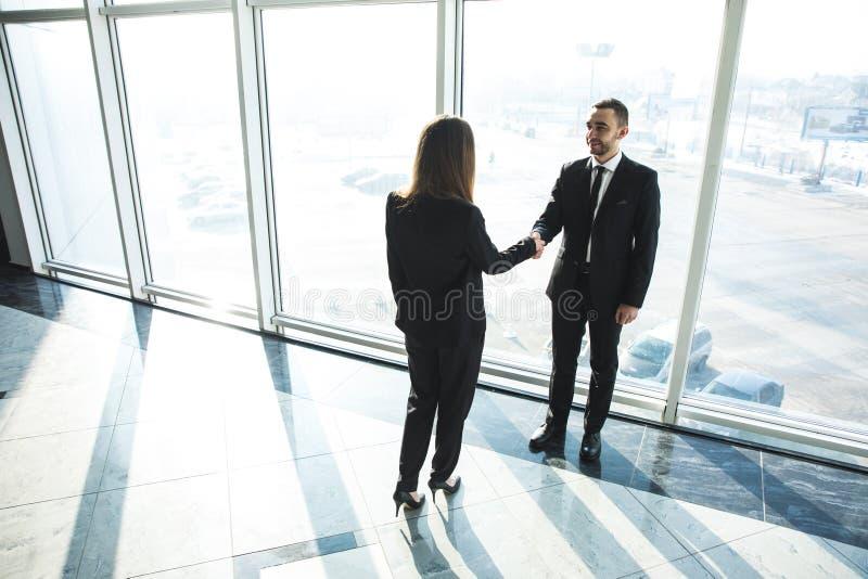 Biznes, praca zespołowa, partnerstwo, współpraca i ludzie pojęć, - ludzie biznesu trząść ręki nad panoramicznym biurem zdjęcia stock
