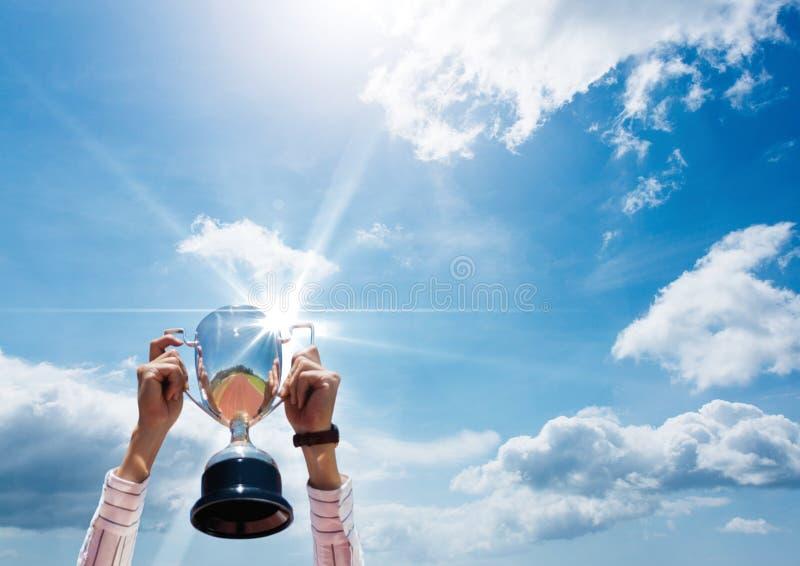 Biznes ręki z trofeum przed niebieskim niebem fotografia stock