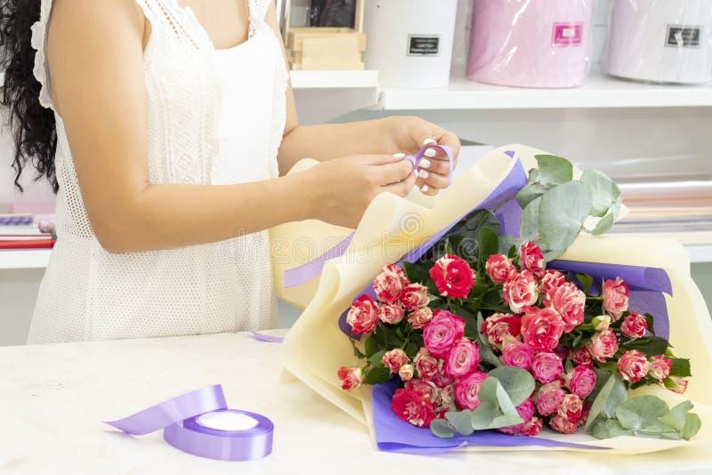 Biznes, sprzedaż i floristry pojęcie, - zamyka w górę kwiaciarni kobiety trzyma wiązkę przy kwiatu sklepem Miękcy cienie świezi k fotografia royalty free