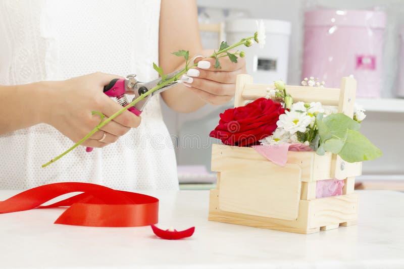 Biznes, sprzedaż i floristry pojęcie, - zamyka w górę kwiaciarni kobiety trzyma wiązkę przy kwiatu sklepem Miękcy cienie świezi k fotografia stock