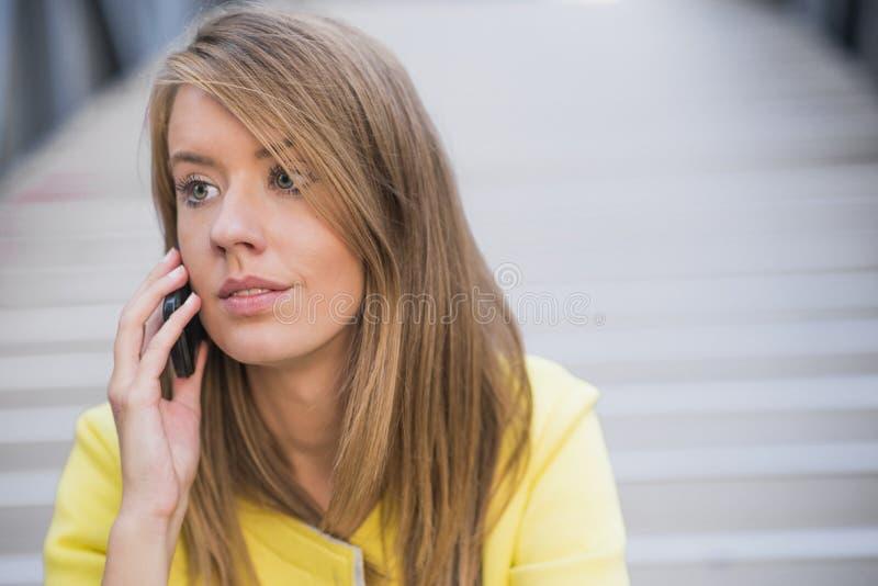 Biznes, technologia i ludzie pojęć, - poważny bizneswoman opowiada nad budynkiem biurowym z smartphone zdjęcia stock