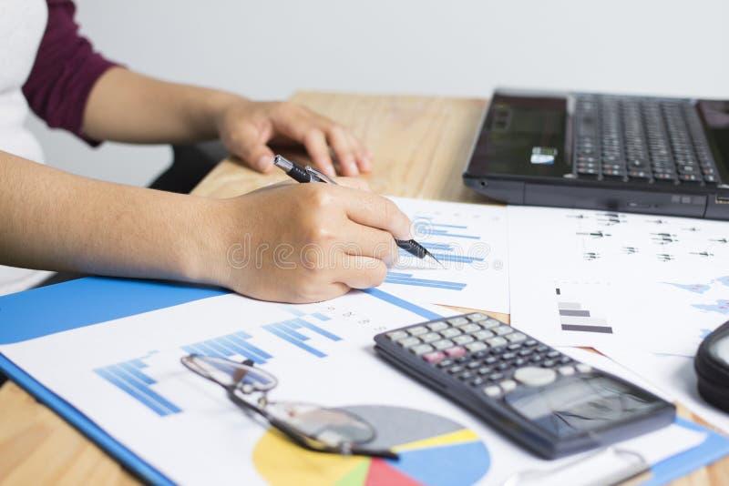 Biznes trzyma wskazuje pióro i kalkulatorów na drewnie fotografia stock