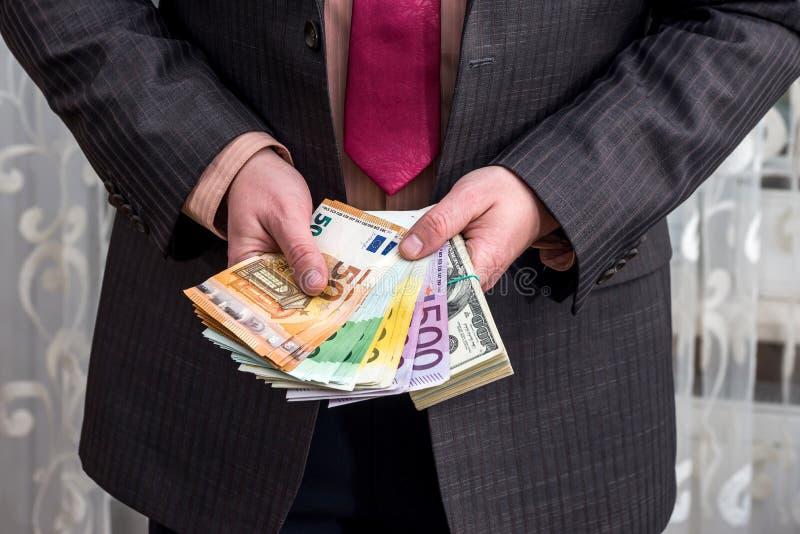 Biznesmenów chwytów paczka dolary i euro zdjęcie royalty free