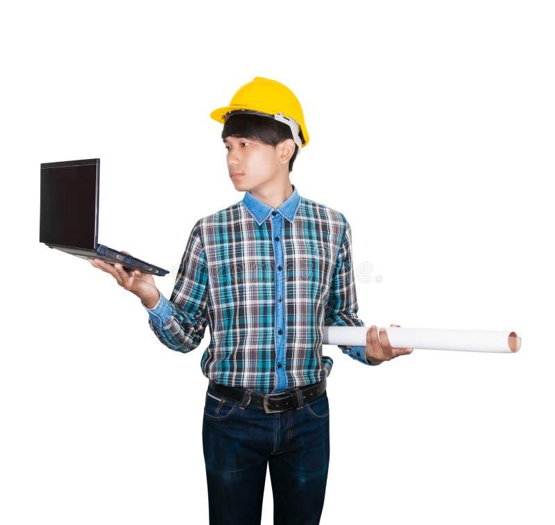 Biznesmenów potomstwa trzymają laptop i staczający się projekty są ubranym żółtego zbawczego hełma klingeryt na białej tło budowi obrazy royalty free