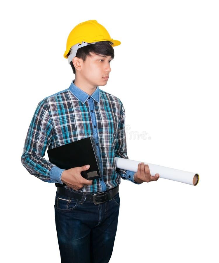 Biznesmenów potomstwa trzymają laptop i staczający się projekty są ubranym żółtego zbawczego hełma klingeryt na białej tło budowi obraz royalty free