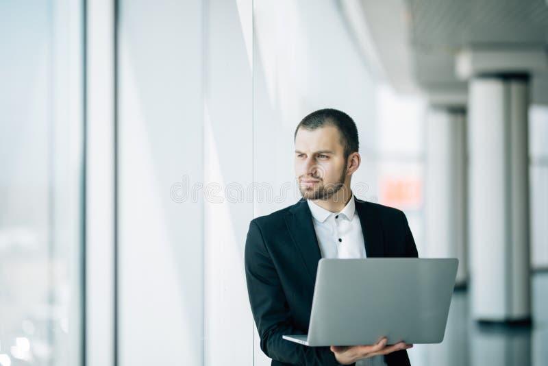Biznesmenów stojaki w jaskrawym powiewnym biurze trzyma otwartego laptop w jego ręki obraz royalty free