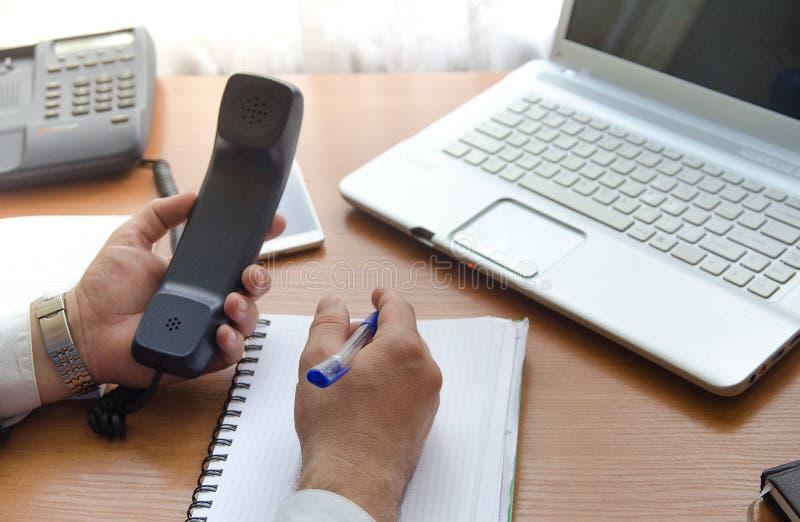 Biznesmenów utrzymania w jego rękach handset robią notatkom w notatniku obrazy royalty free