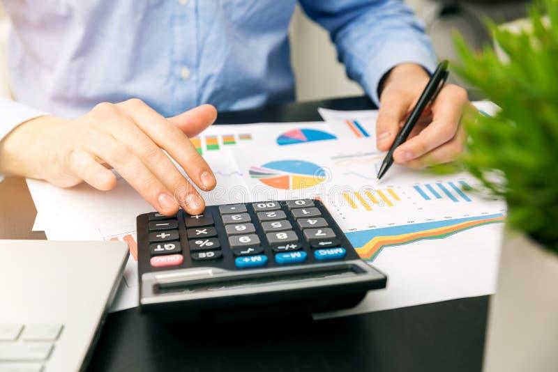 Biznesmen analizuje pieniężnych wykresy i raporty fotografia stock