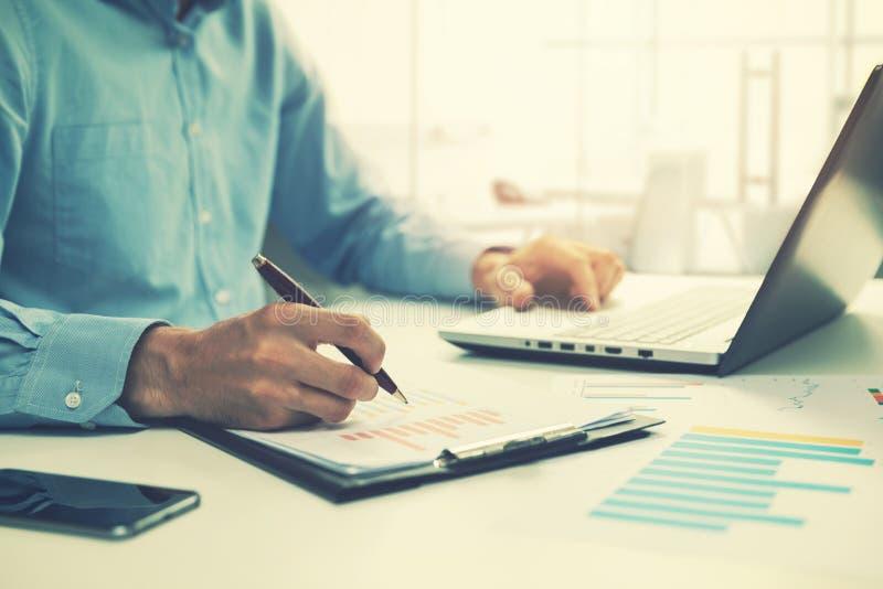 Biznesmen analizuje rocznego biznesowego raport i używa laptop obrazy royalty free