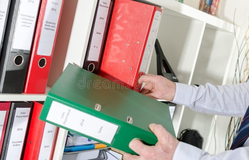 Download Biznesmen Bierze Segregatorów Od Półki Zdjęcie Stock - Obraz złożonej z archiwizujący, mienie: 57650248