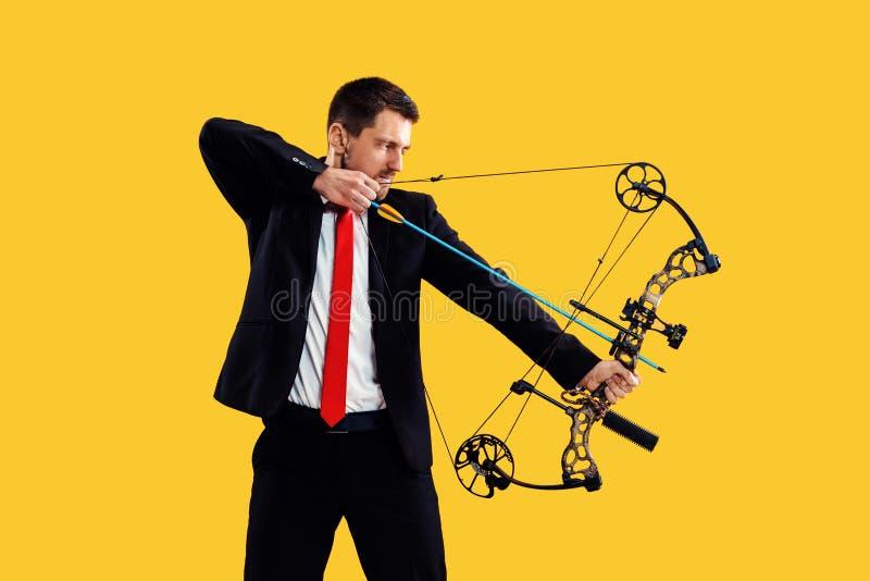 Biznesmen celuje cel z łękiem i strzałą odizolowywającymi na żółtym tle, obraz stock