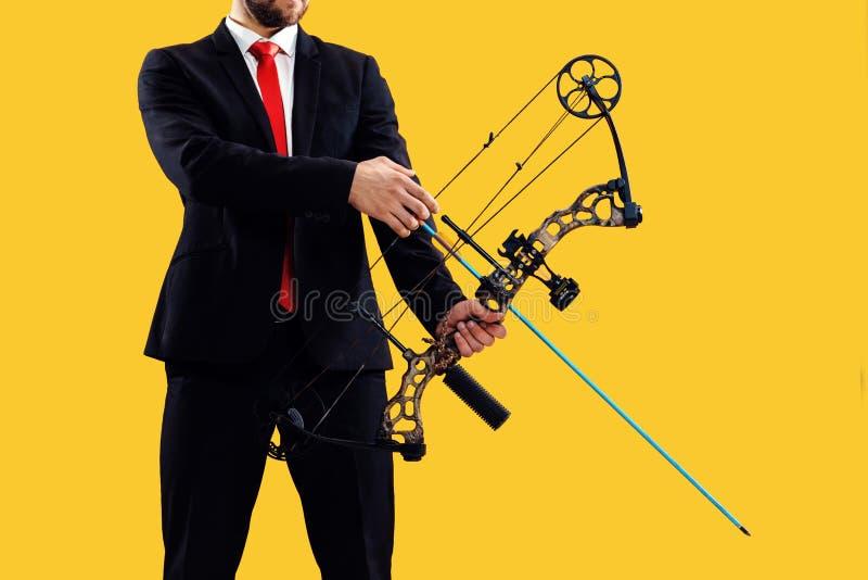 Biznesmen celuje cel z łękiem i strzałą odizolowywającymi na żółtym tle, obrazy stock