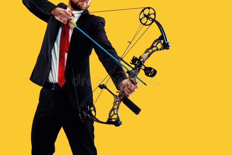 Biznesmen celuje cel z łękiem i strzałą odizolowywającymi na żółtym tle, zdjęcie stock