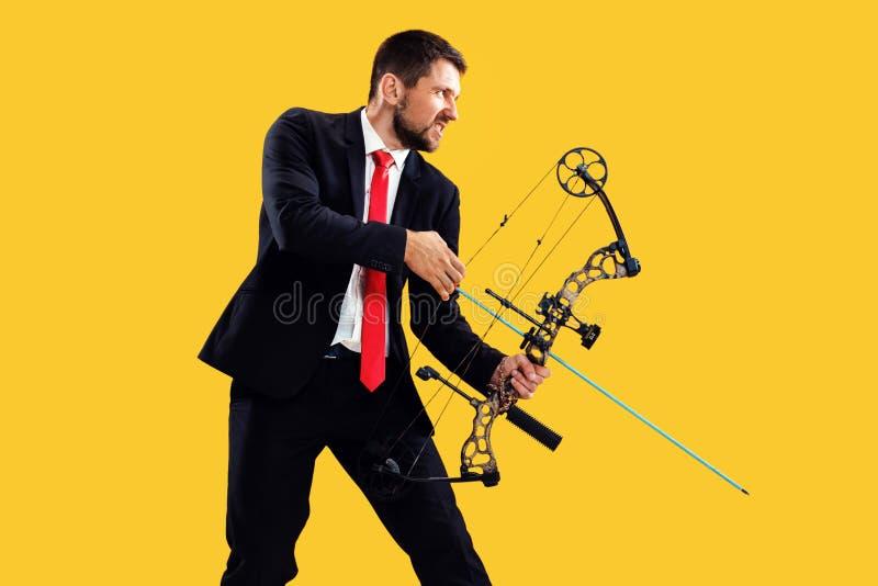 Biznesmen celuje cel z łękiem i strzałą odizolowywającymi na żółtym tle, fotografia royalty free