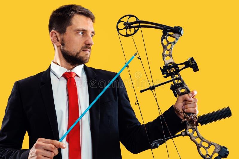 Biznesmen celuje cel z łękiem i strzałą odizolowywającymi na żółtym tle, zdjęcia stock
