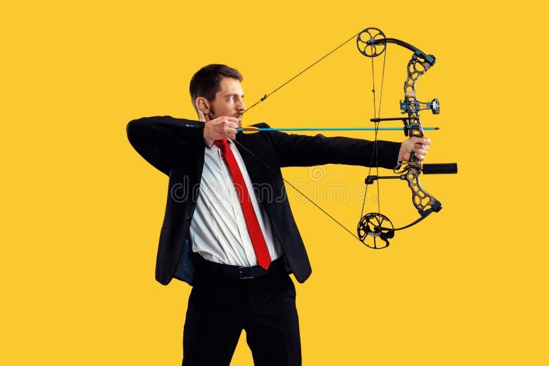 Biznesmen celuje cel z łękiem i strzałą odizolowywającymi na żółtym tle, fotografia stock