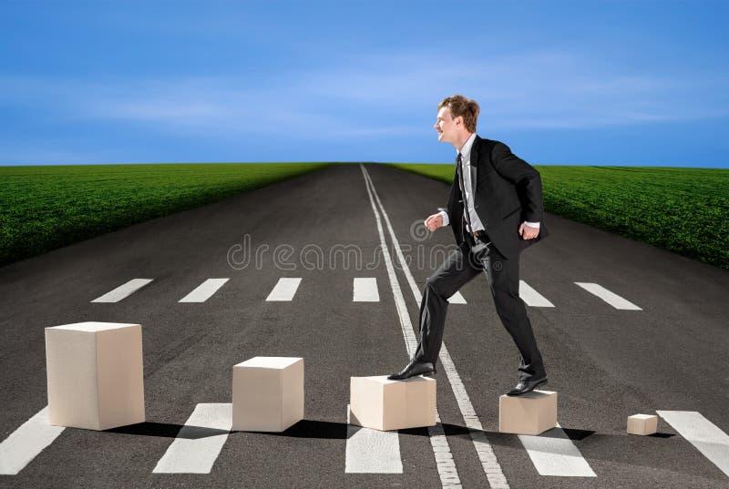 Biznesmen chodzi up na pudełkach na drodze, sposoby pieniężni obraz stock