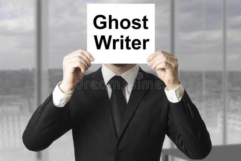 Biznesmen chuje twarz za szyldowym ducha pisarzem obrazy stock