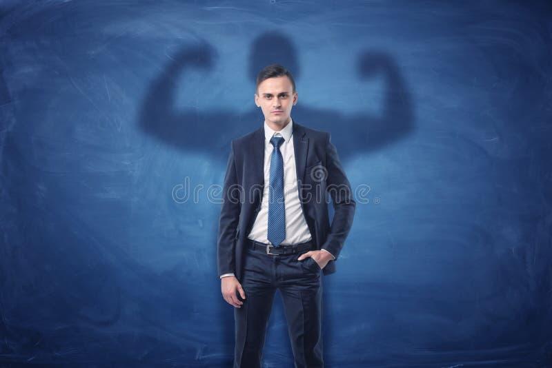 Biznesmen ciska cień duży silny mięśniowy mężczyzna pokazuje jego bicepsy obraz royalty free