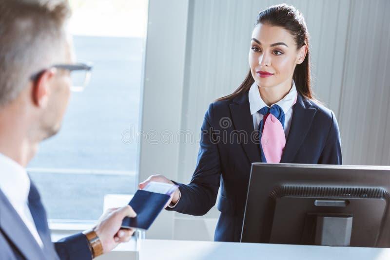 biznesmen daje dokumentom żeński lotniskowy pracownik przy odprawą zdjęcia stock