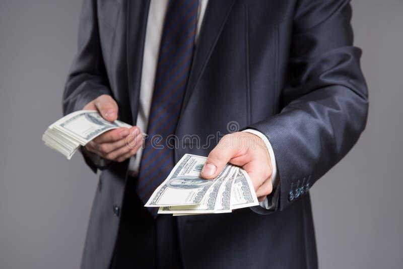 Biznesmen daje dolarom Szary tło fotografia royalty free