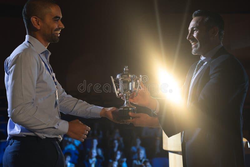 Biznesmen daje trofeum biznesowy męski kierownictwo na scenie w audytorium zdjęcia stock