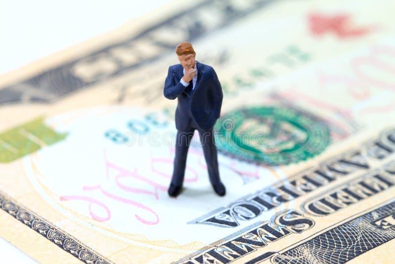 Biznesmen figurka na usa dolara banknocie Biznesowa pozycja na pieniądze pojęciu zdjęcie royalty free