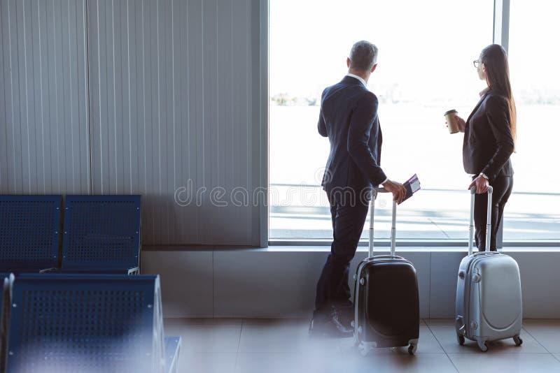 biznesmen i bizneswoman patrzeje okno przy wyjściowym holem obrazy stock