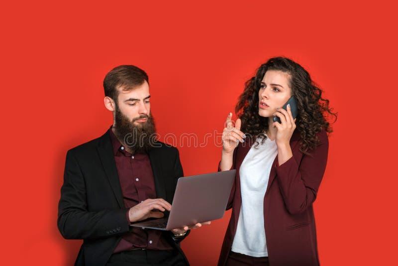 Biznesmen i bizneswoman z gadżetami odizolowywającymi na czerwonym tle fotografia royalty free