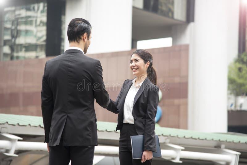 Biznesmen i bizneswomany robi uścisk dłoni zgodzie obrazy stock