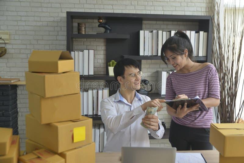 biznesmen i bizneswomany trzyma pieniądze zysk który dostaje formularzowemu sprzedawaniu online produkt zdjęcie stock