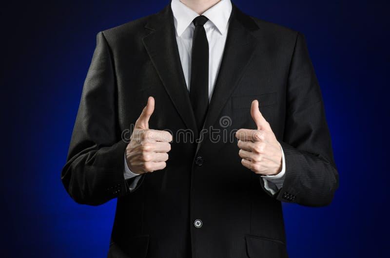 Biznesmen i gesta temat: mężczyzna w czarnym kostiumu białej koszula i pokazywać ręka gestom aprobaty na zmroku - błękitny tło ja zdjęcia royalty free