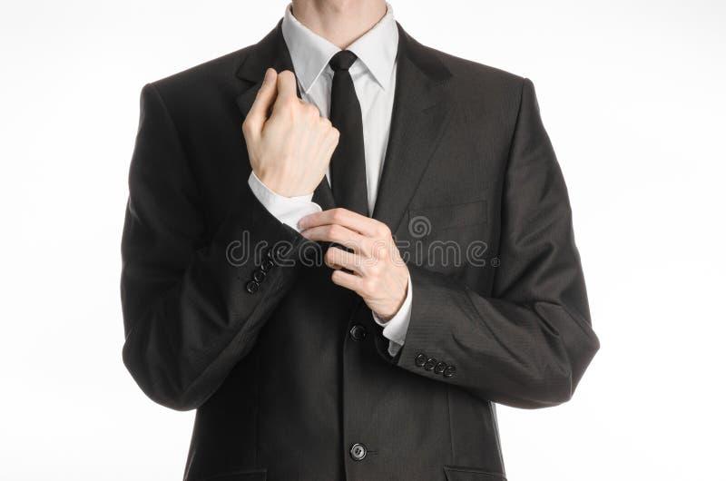 Biznesmen i gesta temat: mężczyzna w czarnym kostiumu z krawata żakietem prostuje jego ręki odizolowywać na białym tle w studiu zdjęcie royalty free