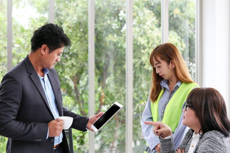 Biznesmen i inżyniery pracuje pokój konferencyjnego z pastylką Trzy pracownika oglądają budowa plan przy biurem Electri obrazy royalty free
