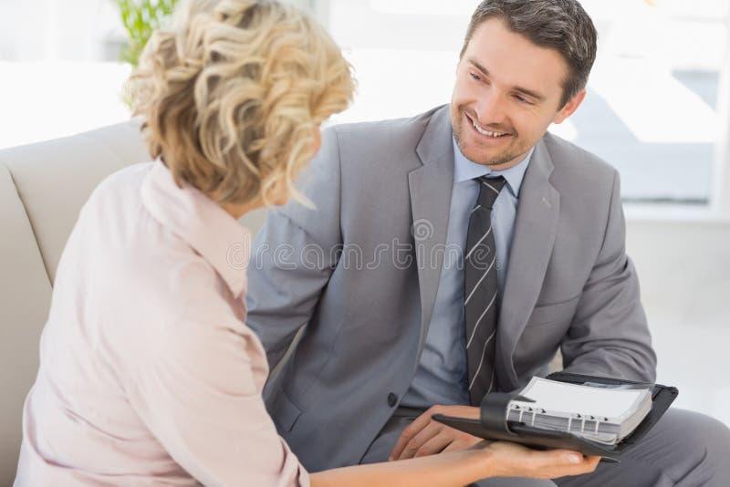 Biznesmen i jego sekretarka z dzienniczkiem w domu zdjęcia royalty free